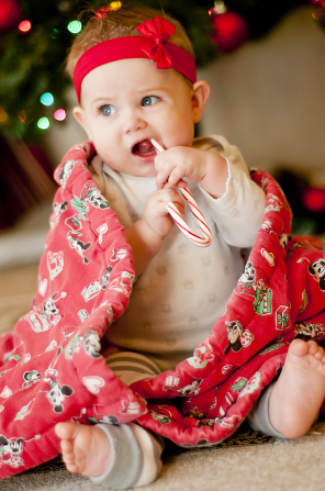 A baby girl eating a candy cane while wrapped in a red blanket and sitting on the floor next to a Christmas tree.