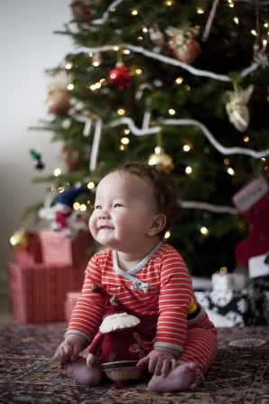 A small baby in red and white striped pajamas smiling and sitting near a decorated Christmas tree in the morning.