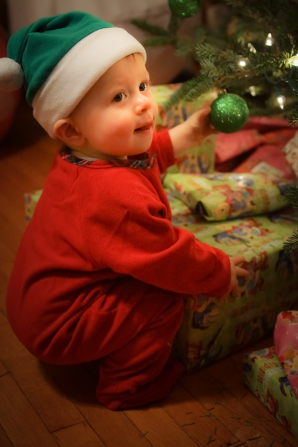 A baby in red pajamas and a Santa hat sits next to the Christmas presents under the tree, holding an ornament in his hand.