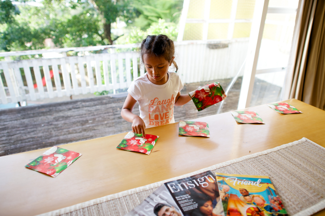 A young girl walks around a wooden table, putting down a row of Christmas-themed napkins for a meal on Christmas Day.