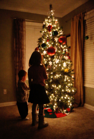 A boy and a girl stand in front of a Christmas tree with the lights turned on.