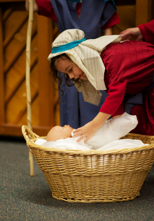 A young girl in a biblical costume bends over a wicker basket to put a plastic baby doll inside during a reenactment of the Nativity.