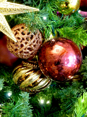 A group of red and gold ornaments on a green Christmas tree with white lights.