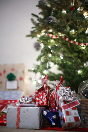 Several sizes and colors of wrapped packages sitting together beneath a lit and decorated Christmas tree.