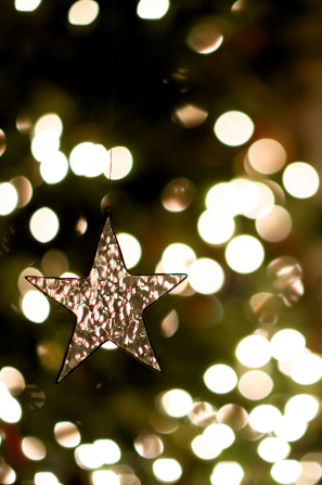 A small glass ornament in the shape of a star hanging on a green Christmas tree lit up with white Christmas lights.