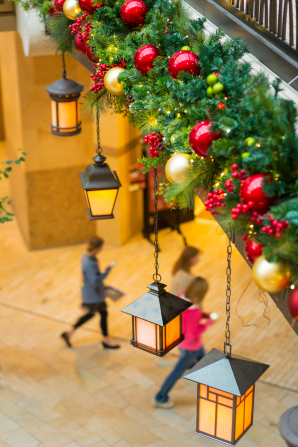 A row of lit lanterns and a decorated pine bough overhanging a stone walkway in the City Creek mall.