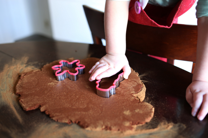 A young child shaping gingerbread Christmas cookies with cookie cutters.