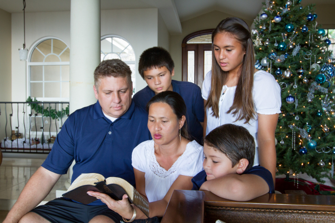 A family of five gathers near the Christmas tree to read from the Bible together.