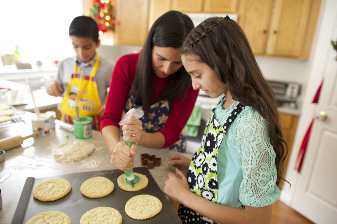 A mother decorating Christmas sugar cookies with her son and daughter in the kitchen.