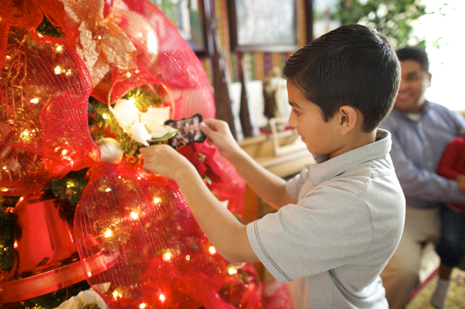A boy places an ornament on a Christmas tree while a man watches in the background.