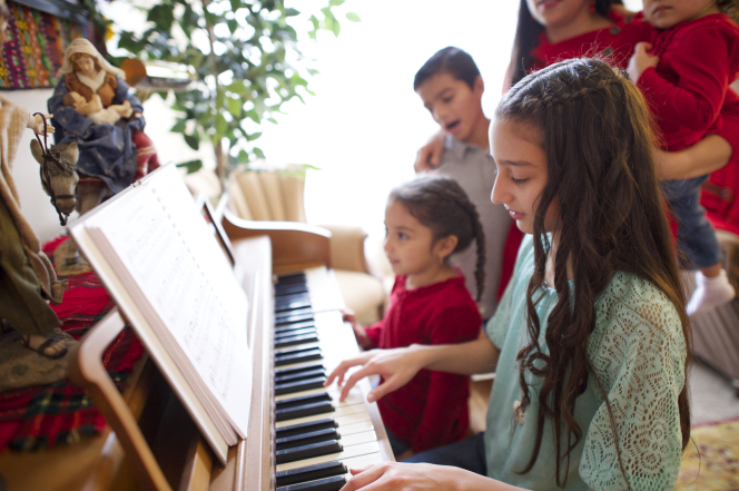 A girl with long brown hair playing a piano while her family members stand and sing beside her.