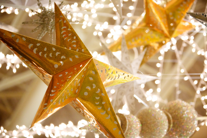 Two stars made of decorative gold foil hang from a ceiling amid silver and white decorations at Christmastime.