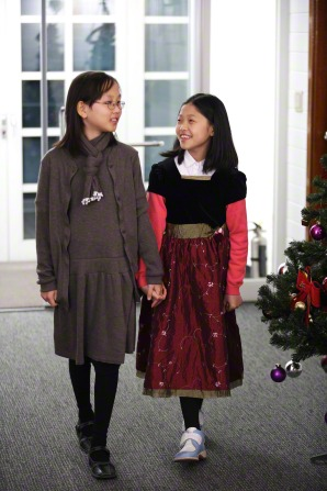 Two girls wearing Christmas dresses hold hands while walking in a Church building.