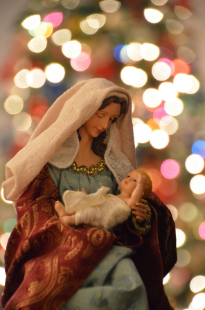 A Nativity figurine of Mary holding the baby Jesus wrapped in white linen, with colorful Christmas lights in the background.
