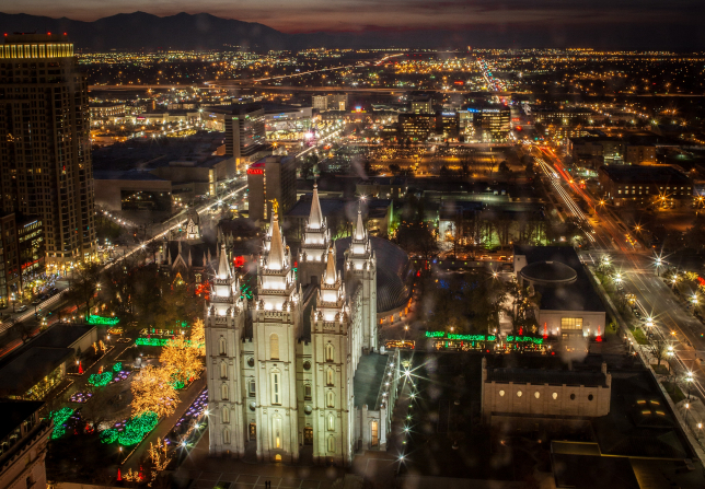 An aerial view of Temple Square and downtown Salt Lake City decorated in Christmas lights.