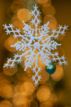 A white glittered Christmas tree ornament in the shape of an intricate snowflake, with blurred golden lights in the background.