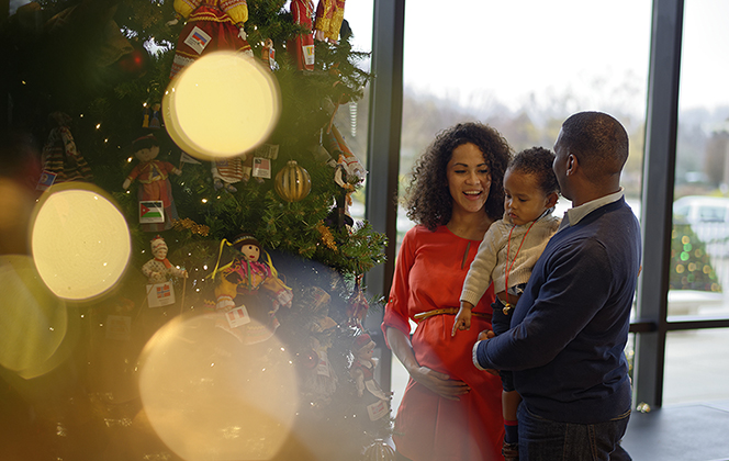 A father, mother, and young son smiling while standing next to a decorated Christmas tree.
