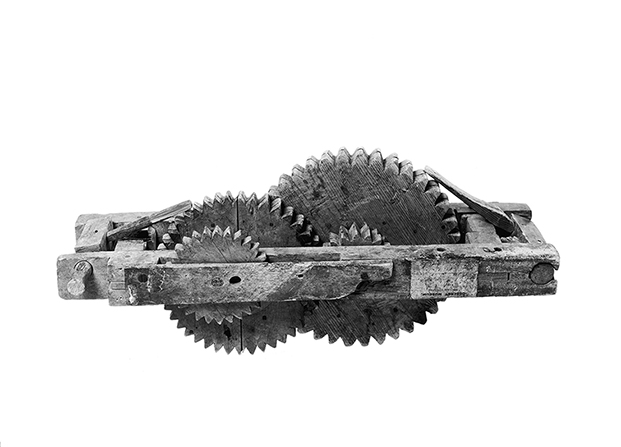 A black-and-white photograph of a wooden odometer with several interlocking wooden gears.