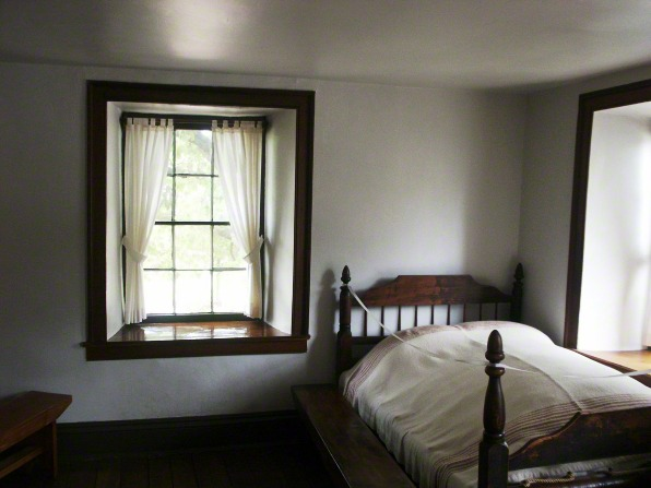 A bed sits to the right of a window in the room of Carthage Jail, where Joseph and Hyrum Smith were martyred.