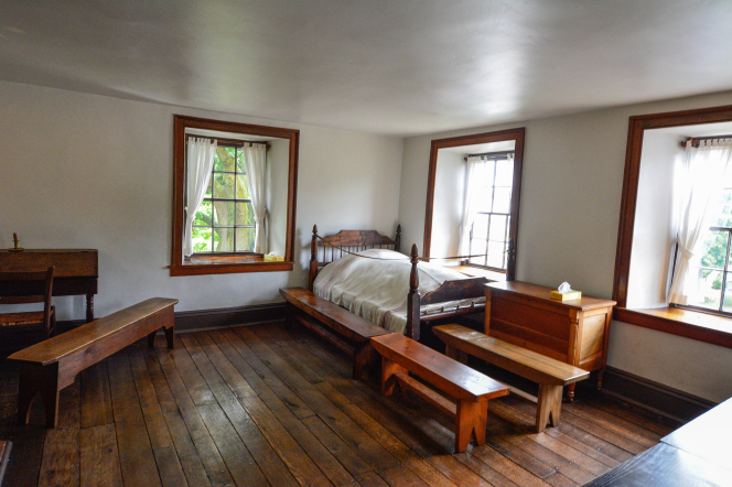 A bed sits in a room with three large windows where Joseph and Hyrum Smith were martyred.