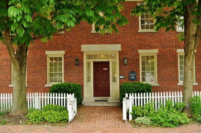 The red-brick home of John Taylor with a white picket fence in front and two trees on either side of the front door.