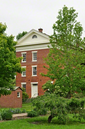 A red-brick building four stories tall with white doors and windows, surrounded by green grass, tall green trees, and shrubbery.