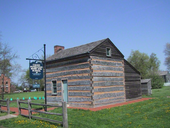 A log cabin with a blue door, known as the Pendleton home and schoolhouse, in Nauvoo, Illinois.