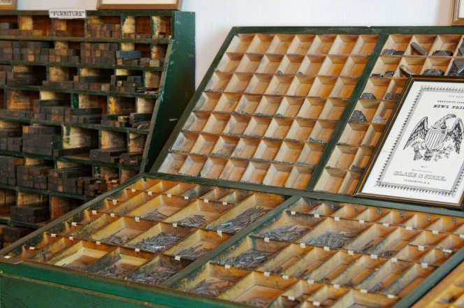 Individual letters used in the Nauvoo print shop letterpress, arranged in green wooden casing.