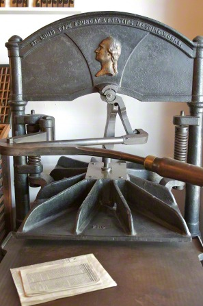 An image of an antique silver printing press with a booklet next to it at the Nauvoo print shop in Illinois.