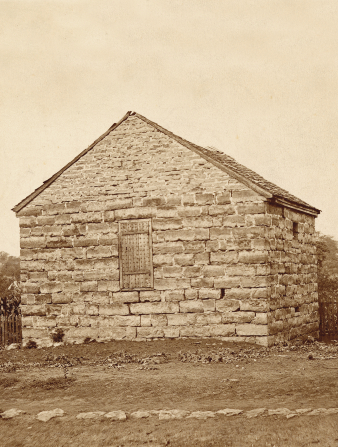 A brown-and-white photograph of Carthage Jail taken in 1896.