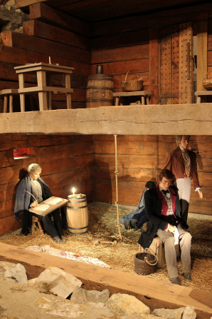 A small replica of Liberty Jail depicting Joseph Smith and two other prisoners.