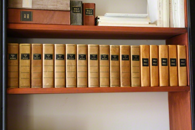 A row of old copies of the Book of Mormon on a shelf in the Grandin Print Shop.