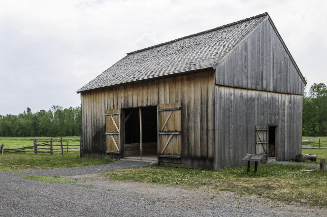 A large wooden barn with the doors wide open on the property of the Smith family farm in Palmyra, New York.