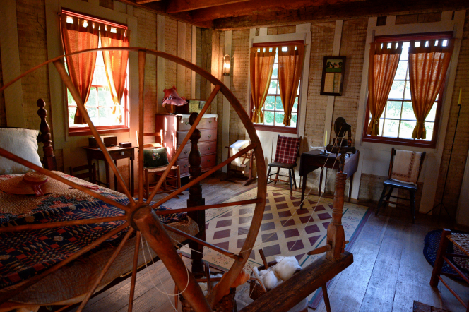 A large spinning wheel, a bed, a dresser, and several chairs in the house on the Smith family farm.
