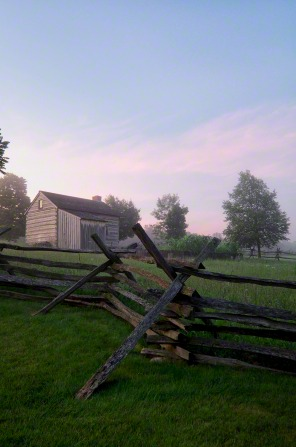 A wooden fence in the foreground and an old log cabin in the background on the Smith family farm in Palmyra, New York.