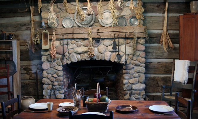 A fireplace, a dining table with plates and a fruit basket, and dried plants hanging from the ceiling in the Peter Whitmer cabin in Fayette, New York.