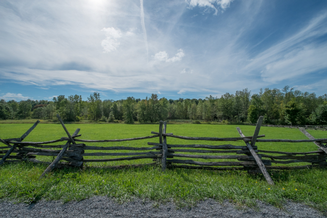 A wooden fence on the Smith family farm, running along the edge of a gravel road, with a green field and trees in the background.