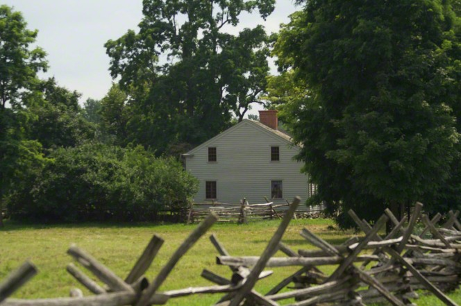 Wooden fences in the foreground and a white wooden-frame home in the background in Palmyra.