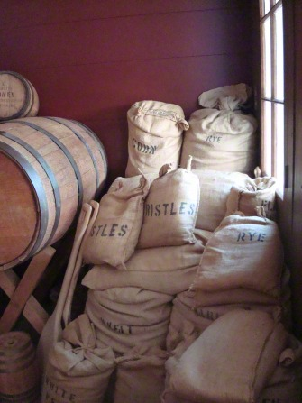 "White sacks labeled ""Corn,"" ""Rye,"" etc. stacked in a corner against a red wall."
