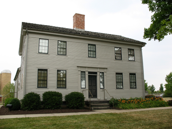 The John Johnson home in Hiram, Ohio, made of white wood, with a black door and black trim on the windows.