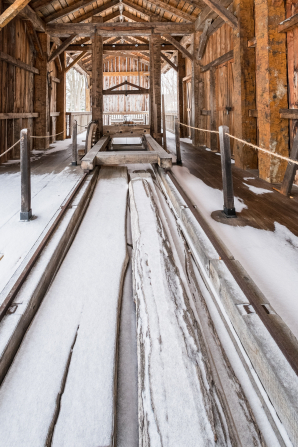 A view of the interior of the sawmill in Kirtland, Ohio, with the ground partially covered in snow.