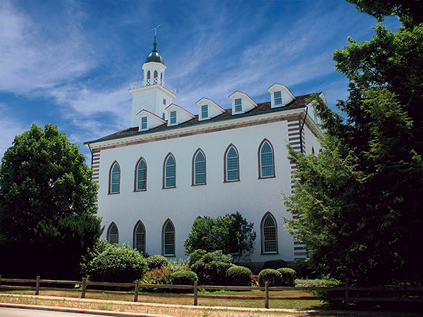 The Kirtland Temple seen from the side between two large green trees, with a small wooden fence running around the grounds.