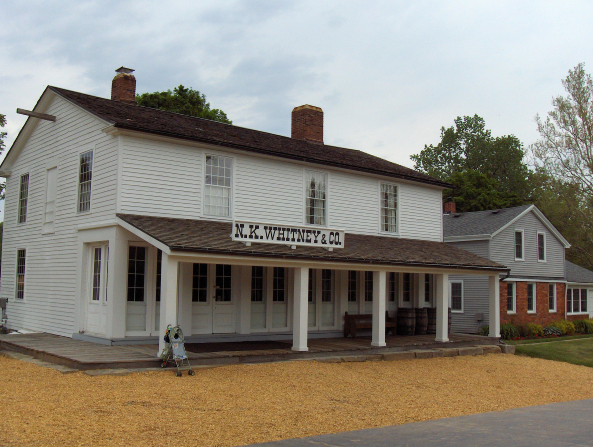 A front exterior view of the Newel K. Whitney store, made of white wood with black shingles.