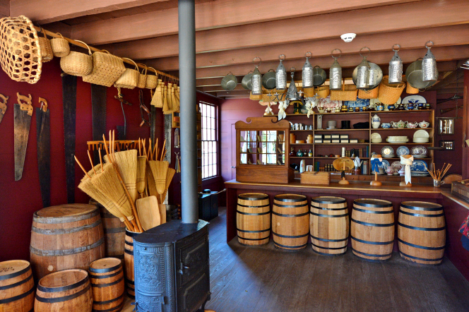 A small wooden store filled with goods from the pioneer era, such as barrels, brooms, saws, pots, and pans.