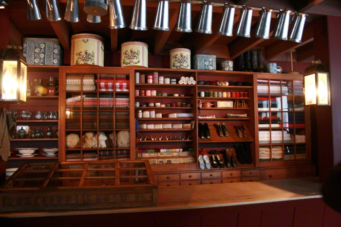 Wooden shelves filled with home items for sale behind the counter in the Newel K. Whitney store.
