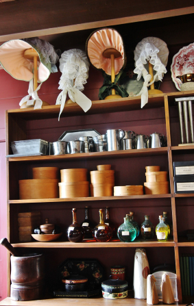 Shelves stacked with goods for purchase, such as round boxes, tin cups, glass bottles, and bonnets with ribbons.