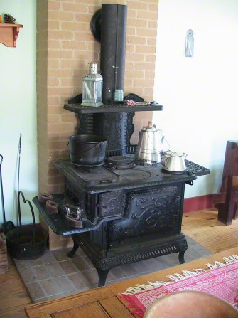 A large black cast-iron stove with silver pots in a room with a wooden floor and bricks in the wall.