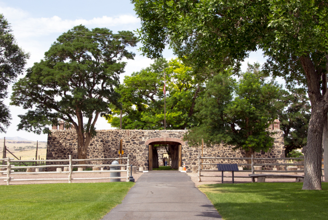 A stone wall with a large gate serving as the entrance to Cove Fort in Utah.