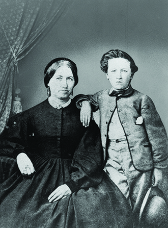 A black-and-white formal photograph of Heber J. Grant as a young boy standing next to his mother, who is in a long black dress.