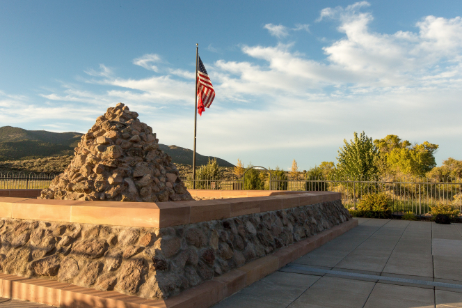 A cairn-style monument on the site of the Mountain Meadows Massacre, with a United States flag nearby.